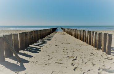 golfbrekers op het strand met zee en horizon